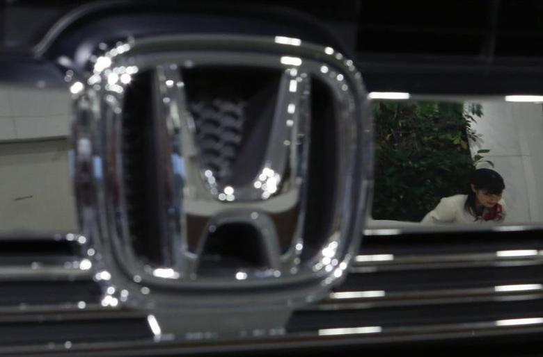 A staff of Honda Motor Co's showroom bows to a visitor as she is reflected in a company logo on a car displayed at company showroom in Tokyo January 30, 2015.  REUTERS/Yuya Shino