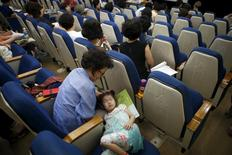 A girl takes a nap next to her grandmother during a child care class for grandparents in Seoul, South Korea, September 1, 2015. REUTERS/Kim Hong-Ji