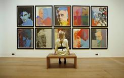 "Gallery employee Maddy Adeane poses with Andy Warhol's ""Ten Portraits of Jews of the Twentieth Century"" (1980)  at the Dulwich Picture Gallery in London June 19, 2012. REUTERS/Luke MacGregor"
