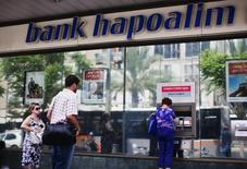 A woman uses an automated teller machine (ATM) outside a Bank Hapoalim branch in Tel Aviv May 30, 2013.  REUTERS/Nir Elias