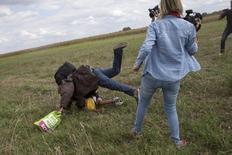 Мигрант с ребенком падают после подножки телеоператора в сборочном пункте в Венгрии. 8 сентября 2015 года. Пнувшая и поставившая подножку убегавшим от полиции мигрантам венгерская тележурналистка сказала, что сожалеет о содеянном, сама будучи матерью, и объяснила поступок приступом паники, а не расизмом. REUTERS/Marko Djurica