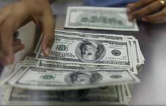 Una mujer cuenta dólares estadounidenses en una casa de cambio en Yangón, 23 de mayo de 2013. Estados Unidos anotó un déficit presupuestario de 64.000 millones de dólares en agosto, una reducción de cerca de un 50 por ciento respecto al mismo período del año pasado, dijo el viernes el Departamento del Tesoro. REUTERS/Soe Zeya Tun