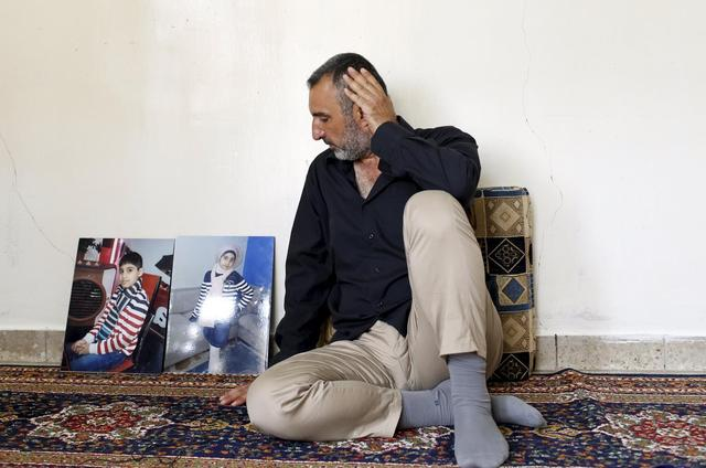Ahmed Hadi Jawwad, whose children drowned while trying to reach Greece, sits next to pictures of them during an interview with Reuters in Baghdad, September 11, 2015.  REUTERS/Thaier al-Sudani