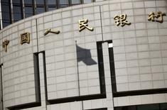La sombra de la bandera nacional china en la sede del banco central del país, en el centro de Pekín, 24 de noviembre de 2014. China permitirá que bancos centrales de otros países realicen operaciones en su mercado interbancario de divisas y transacciones cambiarias de derivados, como canjes y forwards, dijo el lunes el organismo emisor. REUTERS/Kim Kyung-Hoon/FIles