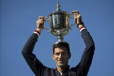 Novak Djokovic of Serbia poses with the champion's trophy in Central Park a day after winning the U.S. Open Championships men's tennis tournament in New York, September 14, 2015. REUTERS/Carlo Allegri