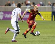 Apr 18, 2015; Sandy, UT, USA; Real Salt Lake midfielder Luke Mulholland (19) dribbles the ball as Vancouver Whitecaps FC midfielder Matias Laba (15) defends during the second half at Rio Tinto Stadium. The Whitecaps won 1-0. Mandatory Credit: Russ Isabella-USA TODAY Sports