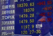Un peatón se refleja en una pantalla que muestra el índice Nikkei y la tasa cambiaria entre el dólar estadounidense y el yen, afuera de una correduría en Tokio, Japón, 9 de septiembre de 2015. Las acciones chinas pusieron fin a una semana volátil con una leve alza el viernes, después de que la Reserva Federal de Estados Unidos se abstuvo de elevar las tasas de interés, citando las preocupaciones sobre la debilidad de la economía mundial. REUTERS/Yuya Shino