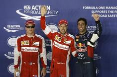 Ferrari Formula One driver Kimi Raikkonen (L) of Finland, team mate Sebastian Vettel (C) of Germany and Red Bull Formula One driver Daniel Ricciardo of Australia pose for photographers after qualifying for the Singapore F1 Grand Prix at the Marina Bay street circuit September 19, 2015. REUTERS/Olivia Harris