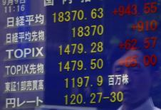 Un peatón se refleja en una pantalla que muestra el índice Nikkei y la tasa cambiaria entre el dólar estadounidense y el yen, afuera de una correduría en Tokio, Japón, 9 de septiembre de 2015. Las bolsas de Asia caían el lunes después de que la decisión de la Reserva Federal de Estados Unidos de mantener las tasas de interés en mínimos históricos planteó nuevas preocupaciones sobre el crecimiento a nivel mundial, sobre todo en China. REUTERS/Yuya Shino