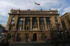 Una bandera mexicana ondea la sede del Banco de México, en Ciudad de México, 3 de enero de 2015. El banco central de México vendió el lunes 200 millones de dólares ofrecidos en una subasta con precio mínimo, a un tipo de cambio ponderado de 16.7059 pesos por billete verde, ante un declive del peso. REUTERS/Edgard Garrido