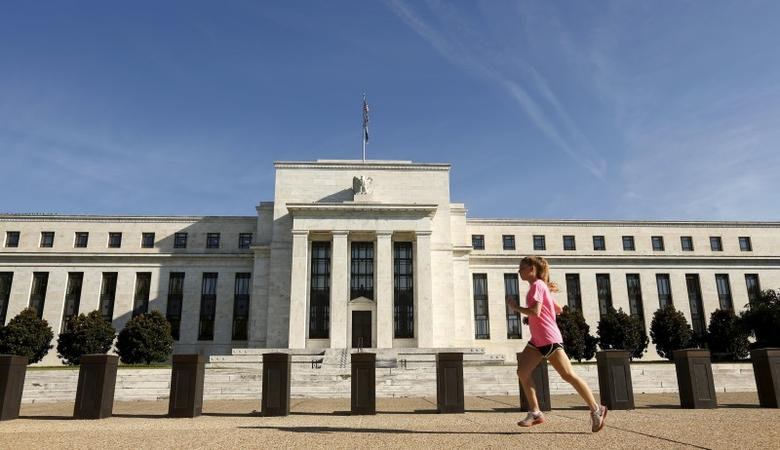 A woman jogs past the Federal Reserve headquarters in Washington September 16, 2015.  REUTERS/Kevin Lamarque