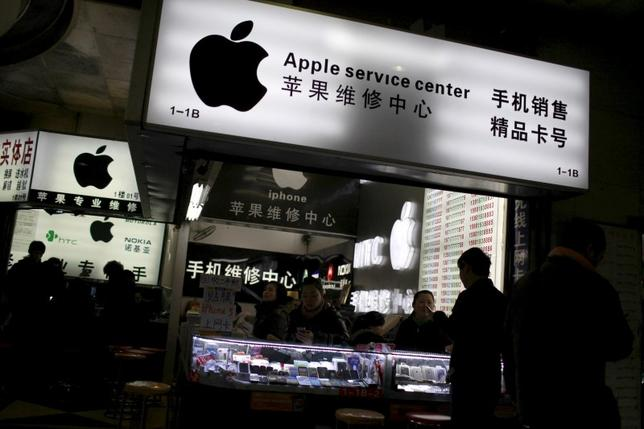 Customers and salespersons are seen at an Apple maintenance service store at a mobile phone market in Shanghai, in this January 24, 2013 file photo.  REUTERS/Aly Song/Files