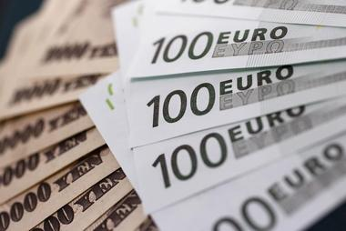 100 Euro notes are spread out next to Japanese 10,000 yen notes at...