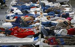 Centre d'accueil temporaire de migrants dans un gymnase à Hanau, près de Munich. L'arrivée d'un grand nombre de réfugiés en Allemagne pourrait augmenter le nombre de chômeurs de 70.000 l'an prochain, estime l'institut d'études IAB de l'Office fédéral du travail. L'Allemagne estime que 800.000 réfugiés et demandeurs d'asile arriveront dans le pays cette année. /Photo prise le 22 septembre 2015/REUTERS/Kai Pfaffenbach