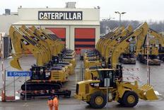 Trabajadores caminan junto a excavadoras en la fábrica de Caterpillar, en Gosselies, Bélgica, 28 de febrero de 2013. Caterpillar Inc dijo el jueves que podría recortar hasta 10.000 puestos de trabajo al 2018 como parte de unos planes de reestructuración y reducción de costos destinados a ahorrar hasta 1.500 millones de dólares anuales. REUTERS/Eric Vidal