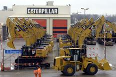Workers walk past Caterpillar excavator machines at a factory in Gosselies, in this file photo taken February 28, 2013. REUTERS/Eric Vidal