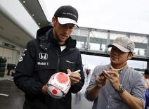 McLaren Formula One driver Jenson Button (L) of Britain gives his autoraph to a fan at the paddock area after the second practice session in Suzuka, Japan, September 25, 2015, ahead of Sunday's Japanese F1 Grand Prix. REUTERS/Thomas Peter