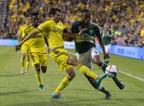 Sep 26, 2015; Columbus, OH, USA; Columbus Crew SC defender Michael Parkhurst (4) clears the ball away from an attacking Portland Timbers forward Fanendo Adi (9) in the second half of the game at MAPFRE Stadium. The Portland Timbers beat the Columbus Crew SC 2-1. Mandatory Credit: Trevor Ruszkowski-USA TODAY Sports