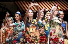 Models take selfie with mobile phones during the parade at the end of the Dolce & Gabbana Spring/Summer 2016 collection during Milan Fashion Week in Italy, September 27, 2015.  REUTERS/Alessandro Garofalo