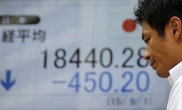 Un hombre camina delante de un tablero electrónico que muestra el índice Nikkei de Japón, afuera de una correduría en Tokio, 1 de septiembre de 2015. El índice Nikkei de la bolsa de Tokio cayó el lunes luego de que los inversores recogieron ganancias de un avance registrado en la sesión previa, antes de unos importantes indicadores económicos que serán reportados esta semana en Japón, China y Estados Unidos.  REUTERS/Toru Hanai