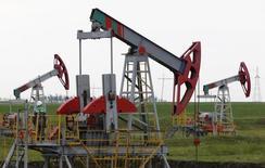 Станки-качалки на нефтяном месторождении в Башкирии. 11 июля 2015 года. Российские власти отмели идею Минфина изменить формулу налога на добычу полезных ископаемых (НДПИ) на нефть, но продолжат поиски фискальных методов в нефтегазовой отрасли для пополнения прохудившегося бюджета. REUTERS/Sergei Karpukhin