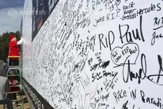"A man signs a large condolence card during an unofficial memorial event for ""Fast & Furious"" star Paul Walker in Santa Clarita, California December 8, 2013. REUTERS/Jonathan Alcorn"