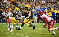 Sep 28, 2015; Green Bay, WI, USA;  Green Bay Packers quarterback Aaron Rodgers (12) scrambles between Kansas City Chiefs linebacker Derrick Johnson (56) and linebacker Tamba Hali (91) in the first quarter at Lambeau Field. Mandatory Credit: Benny Sieu-USA TODAY Sports