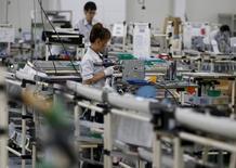 Empleados de una planta de ensamblaje de Glory Ltd, fabricante de máquinas de cambio automático, en Kazo, al norte de Tokio el 1 de julio de 2015. La producción industrial de Japón cayó inesperadamente por segundo mes consecutivo en agosto, lo que generó temores de que una baja prolongada pueda disipar una recuperación económica vacilante y aumentó las expectativas de nuevas medidas de estímulo del Banco de Japón para reactivar el crecimiento. REUTERS/Issei Kato