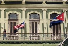 A man stands near the national flags of the U.S. and Cuba (R) on the balcony of a hotel being used by the first U.S. congressional delegation to Cuba since the change of policy announced by U.S. President Barack Obama on December 17, in Havana, January 19, 2015. The United States will urge Cuba to lift travel restrictions on U.S. diplomats and agree to establish U.S. and Cuban embassies in historic talks in Havana this week aimed at restoring relations, a senior State Department official said on Monday. REUTERS/Stringer (CUBA - Tags: POLITICS) - RTR4M2H1