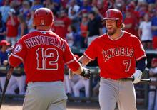 Oct 3, 2015; Arlington, TX, USA; Los Angeles Angels left fielder Collin Cowgill (7) celebrates his run with second baseman Johnny Giavotella (12) against the Texas Rangers during the ninth inning of a baseball game at Globe Life Park in Arlington. The Angels won 11-10. Mandatory Credit: Jim Cowsert-USA TODAY Sports