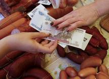Покупатель платит продавцу за продукты на рынке в Красноярске 29 июля 2015 года. Потребительские цены в РФ выросли в сентябре 2015 года на 0,6 процента к предыдущему месяцу и на 15,7 процента - к аналогичному периоду прошлого года, что чуть лучше, чем  прогнозировали аналитики. REUTERS/Ilya Naymushin