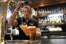 Funcionária enchendo copos de cerveja em Sydney.  21/06/2011     REUTERS/Tim Wimborne