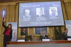Фотографии обладателей Нобелевской премии по химии 2015 года на пресс-конференции в Стокгольме 7 октября 2015 года. Нобелевскую премию по химии 2015 года получили британец Томас Линдаль и американцы Пол Модрич и Азиз Санкар за разработки в области ДНК, сообщила Шведская королевская академия наук. REUTERS/Fredrik Sandberg/TT News Agency