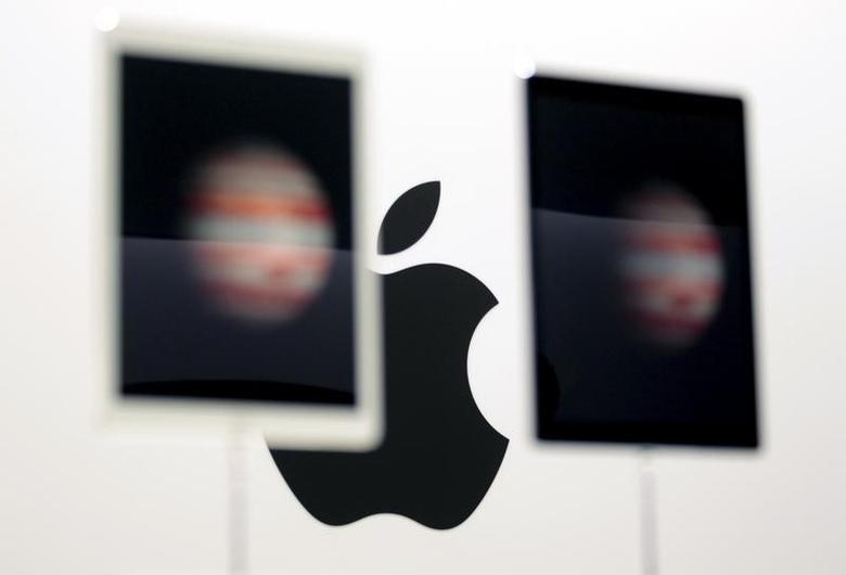 The Apple logo is seen behind new Apple iPad Pros on display during an Apple media event in San Francisco, California, September 9, 2015. REUTERS/Beck Diefenbach