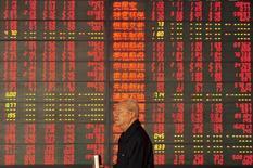 Un inversor camina junto a un tablero electrónico que muestra la información de las acciones, en una correduría en Fuyang, provincia de Anhui, China, 9 de octubre de 2015. Las acciones chinas repuntaron el viernes en línea con un avance de mercados globales en medio de las expectativas cada vez mayores de que la Reserva Federal de Estados Unidos esperará más tiempo antes de elevar las tasas de interés. REUTERS/China Daily