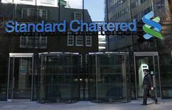 Un hombre camina junto a la oficina central de Standard Chartered en Londres, 27 de febrero de 2015. El nuevo presidente ejecutivo de Standard Chartered, Bill Winters, planea reducir hasta en una cuarta parte los cargos directivos del banco para reducir costos, en una decisión que generaría la pérdida de casi 1.000 puestos de trabajo de alto rango.  REUTERS/Eddie Keogh