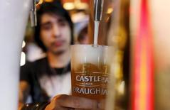 Бармен наливает пиво производства SAB Miller в баре в Кейптауне. 16 сентября 2015 года. Предложение Anheuser Busch InBev о покупке базирующейся в Лондоне пивоваренной компании SAB Miller за $115,3 миллиарда выводит объем объявленных сделок слияний и поглощений (M&A) в мире к $3,38 триллиона - к самому высокому с начала года показателю для этого рынка за период с 1980 года, следует из данных Thomson Reuters. REUTERS/Mike Hutchings