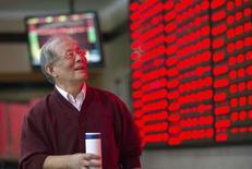 """Un inversor mira un tablero electrónico que muestra la información de las acciones, en una correduría en Nanjing, China, 12 de octubre de 2015. Las acciones chinas saltaron más de un 3 por ciento el lunes a su nivel más alto en siete semanas después de que el banco central tomó nuevas medidas para inyectar liquidez a la economía y de que un funcionario dijo que la corrección del mercado de valores """"casi ha terminado"""". REUTERS/China Daily"""
