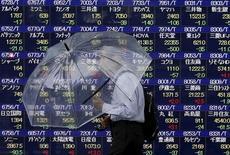 Un hombre camina junto a un tablero que muestra la información de las acciones en una correduría en Tokio, 8 de septiembre de 2015. Las bolsas de Asia subían el lunes, extendiendo un repunte en momentos en que los inversores compraban acciones ligadas al sector industrial y de materias primas, y el dólar perdía terreno al reducirse las expectativas de un alza de las tasas de interés en Estados Unidos este año. REUTERS/Issei Kato