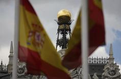 El domo del Banco de España visto detrás de unas banderas españolas en Madrid, jun 19 2013. El presupuesto español corre riesgo de infringir las normas fiscales europeas en 2016 debido a que está basado en una previsión de crecimiento muy optimista que no tiene en cuenta la exposición del país a la ralentización de los mercados emergentes, dijo el lunes la Comisión Europea en un informe.   REUTERS/Sergio Perez