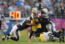 Oct 12, 2015; San Diego, CA, USA; Pittsburgh Steelers running back Le'Veon Bell (26) runs against the San Diego Chargers linebacker Denzel Perryman (52) and Donald Butler (56) at Qualcomm Stadium. Mandatory Credit: Kirby Lee-USA TODAY Sports