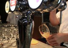 Бармен наливает пиво в Брюсселе 24 апреля 2013 года. SABMiller согласилась на пятое предложение о покупке со стороны Anheuser-Busch InBev, после того как крупнейший пивовар в мире увеличил сумму до 69 миллиардов фунтов ($106 миллиардов). REUTERS /Yves Herman