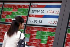 Una mujer mira una pantalla que muestra el índice Nikkei y la tasa cambiaria entre el dólar estadounidense y el yen, afuera de una correduría en Tokio, 25 de agosto de 2015.El índice Nikkei de la bolsa de Tokio cayó el martes luego de que los inversores recogieron ganancias de los avances de la semana anterior, mientras que un declive en los precios del crudo llevó a una ola de ventas de las acciones ligadas al petróleo. REUTERS/Thomas Peter