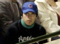 Steve Bartman, the Cubs fan scapegoated for a missed catch in a 2003 playoff game, sits in the stands in the eighth inning of Game 6 of the National League Championship Series in Chicago, October 14, 2003. REUTERS/Allen Fredrickson