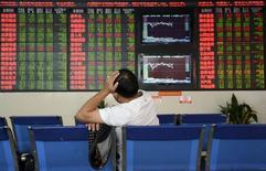 Un inversor frente a un tablero electrónico que muestra la información de las acciones, en una correduría en Fuyang, China, 14 de octubre de 2015. Las acciones chinas cayeron el miércoles, un movimiento que los analistas dijeron parece reflejar una toma de ganancias tras los fuertes avances recientes. REUTERS/China Daily
