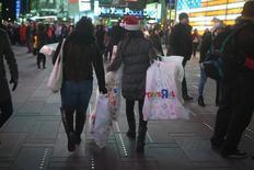 Mujeres caminan con bolsas de compras de la tienda Toys R US, a través de Times Square, en Nueva York, 27 de noviembre de 2014. Las ventas minoristas de Estados Unidos subieron levemente en septiembre debido a que precios más bajos de la gasolina afectaron los ingresos en las estaciones de servicio, pero avances en las compras de autos y de otros bienes apuntaron a una sólida demanda nacional. REUTERS/Carlo Allegri