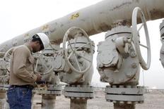Imagen de archivo de un trabajador revisando unas válvulas en un pozo petrolero en Basra, Irak, oct 13, 2014. Irak, el segundo mayor productor de la OPEP, espera elevar la producción petrolera aún más el año próximo y vender volúmenes récord de crudo a clientes desde su terminal del sur, dijo una fuente iraquí del sector.   REUTERS/Essam Al-Sudani