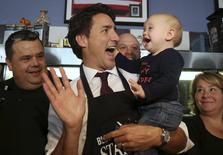 Liberal leader Justin Trudeau holds a baby during a campaign stop at restaurant in Welland, Ontario October 14, 2015. Canadians will go to the polls in a federal election on October 19. REUTERS/Chris Wattie