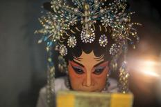 A member of a Chinese opera troupe looks on as she applies make-up before performing at a shrine during the annual vegetarian festival in Bangkok late October 14, 2015. REUTERS/Athit Perawongmetha