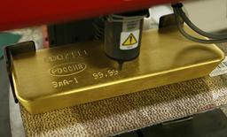 Станок гравирует слиток золота на заводе Красцветмет в Москве 27 февраля 2014 года. Золотовалютные резервы РФ выросли за прошлую неделю до $373,8 миллиарда, что является максимальным значением с 6 февраля текущего года, следует из данных Банка России. REUTERS/Ilya Naymushin